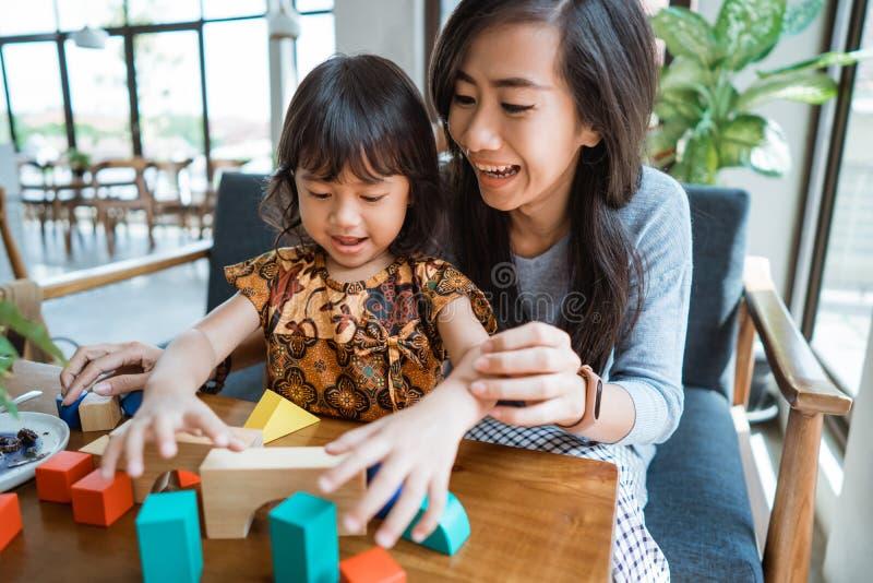 Moder och unge som spelar med träkvarteret royaltyfria foton