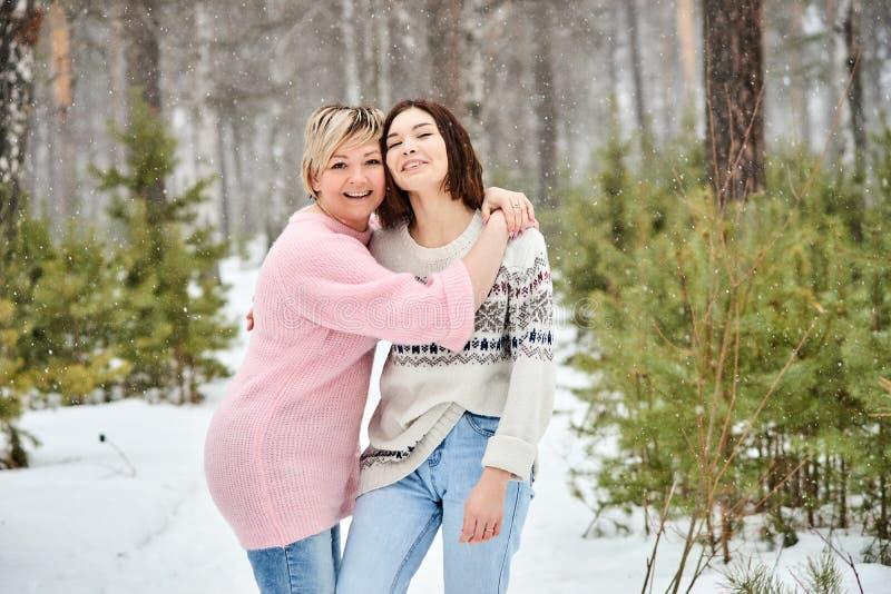 Moder och vuxen dotter som går i vinterskogsnöfall royaltyfri foto