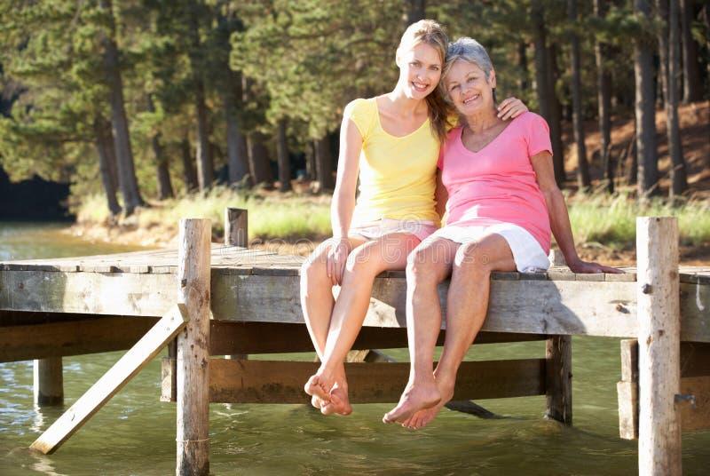Moder- och vuxen människadotter som sitter vid laken arkivfoto