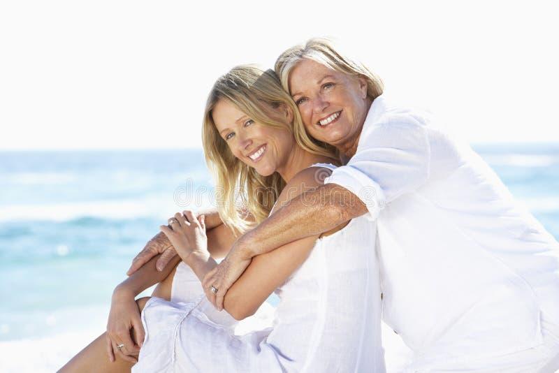 Moder- och vuxen människadotter som tillsammans sitter på stranden royaltyfri bild