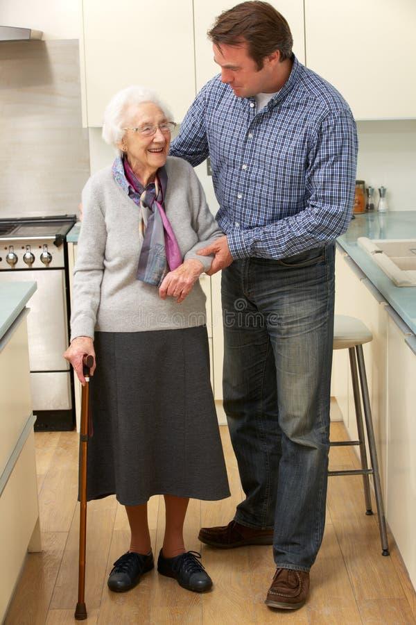 Moder- och vuxen människason i kök royaltyfria bilder