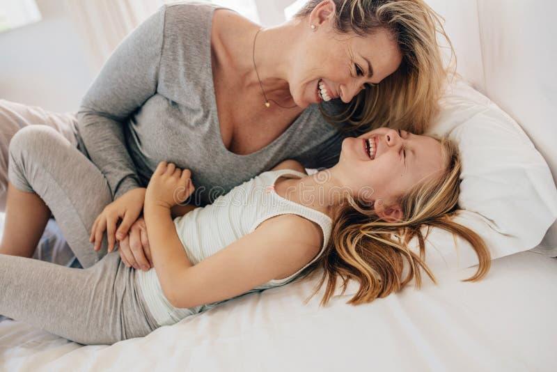 Moder på säng som spelar med hennes dotter royaltyfri bild