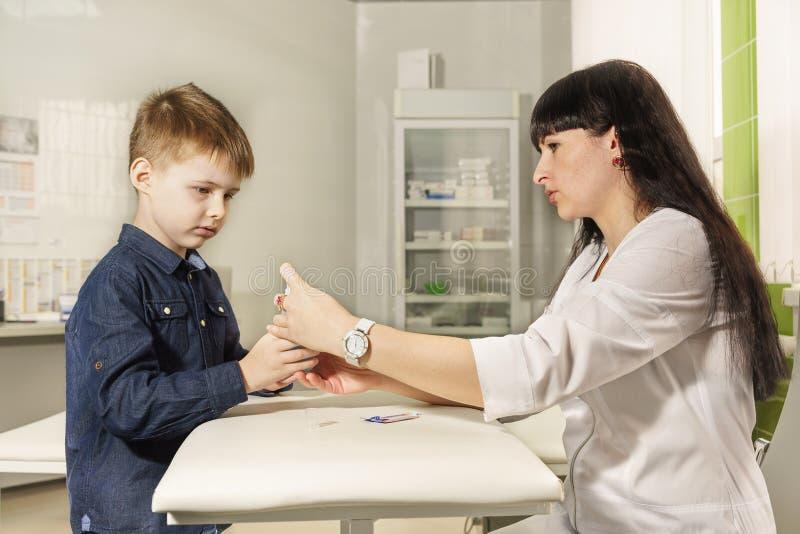 Moder - sjuksköterskan undervisar den lilla sonen att desinficera sår i snitt r royaltyfri fotografi
