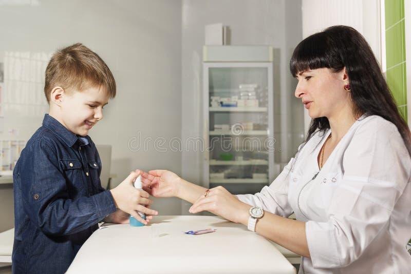Moder - sjuksköterskan undervisar den lilla sonen att desinficera sår med sprej för snitt r royaltyfri bild