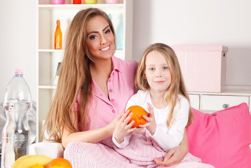Moder som äter frukt med barnet arkivfoton