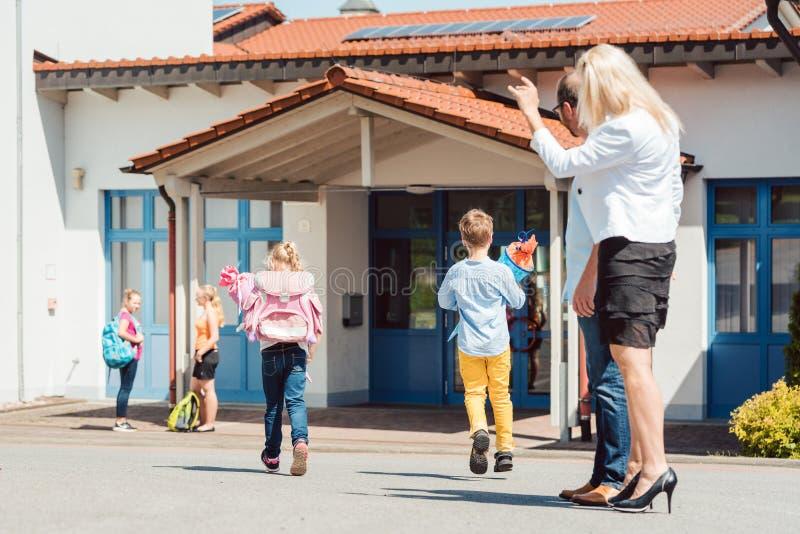 Moder som önskar hennes dotter en lycklig dag på skola royaltyfri fotografi