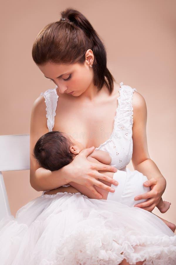 Moder som ammar hennes barn arkivbild