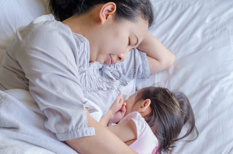 Moder som ammar hennes barn på säng arkivfoton