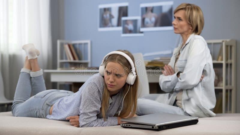 Moder som argumenterar med den tonåriga dottern för att spendera för mycket tid i sociala nätverk royaltyfri bild