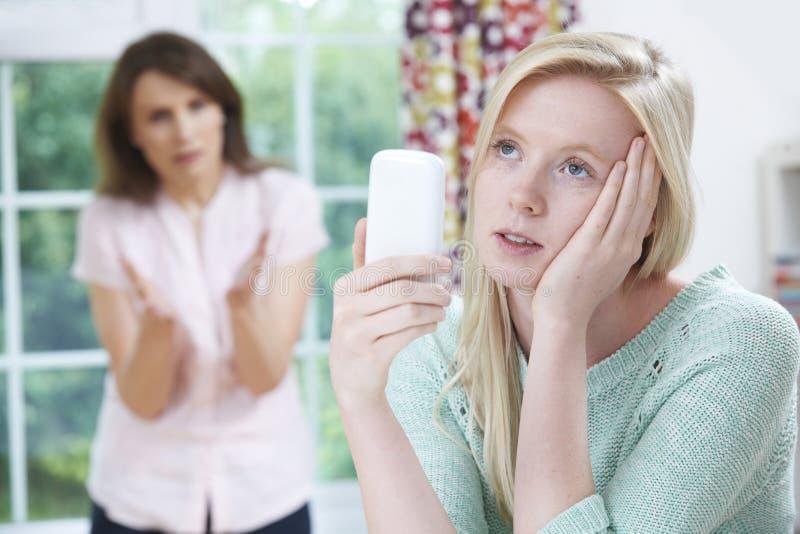 Moder som argumenterar med den tonårs- dottern över bruk av mobiltelefonen royaltyfria bilder