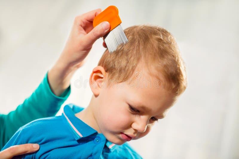 Moder som behandlar sons hår mot löss royaltyfri foto