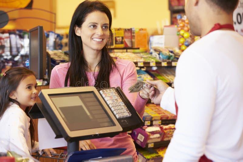 Moder som betalar för familjshopping på kontrollen med kortet arkivfoto