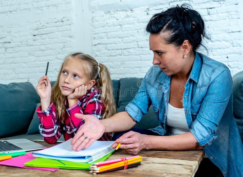Moder som blir frustrerad med dotterstunden som gör läxa som hemma sitter på soffan i lärande svårighetsläxabarnuppfostran royaltyfri fotografi