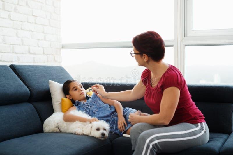 Moder som dåligt kontrollerar temperatur till dottern med termometern arkivfoto