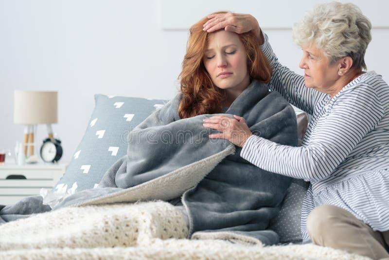 Moder som dåligt mäter temperatur för dotter` s royaltyfria foton