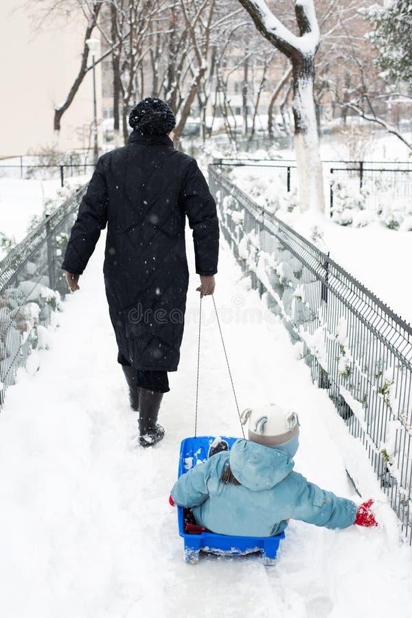 Moder som drar ungen på pulkan royaltyfri fotografi
