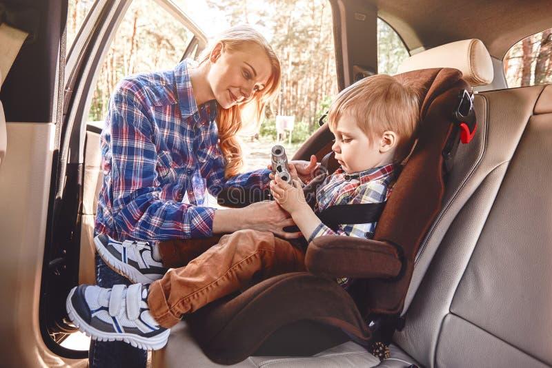 Moder som fäster henne för att behandla som ett barn pojken, att sitta i en bil i säkerhetsstol Familjvägtur royaltyfri fotografi