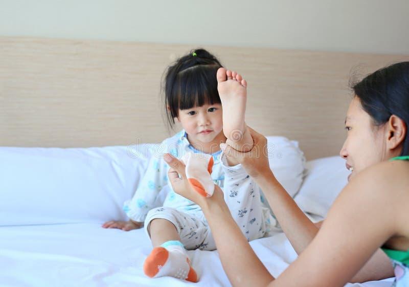 Moder som försöker att sätta sockor för hennes dotter på sängen royaltyfri bild