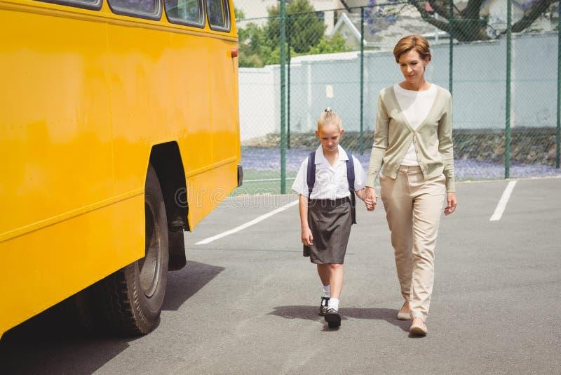 Moder som går hennes dotter till skolbussen royaltyfri bild