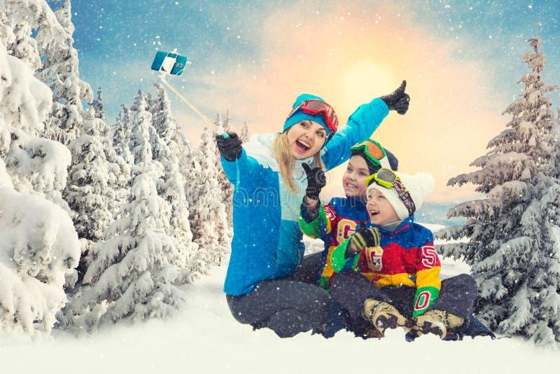 Moder som går med barn i en snöig skogvintergyckel royaltyfri fotografi