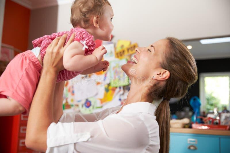Moder som går tillbaka från arbete som kramar den unga dottern royaltyfri bild