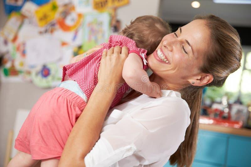 Moder som går tillbaka från arbete som kramar den unga dottern arkivbild