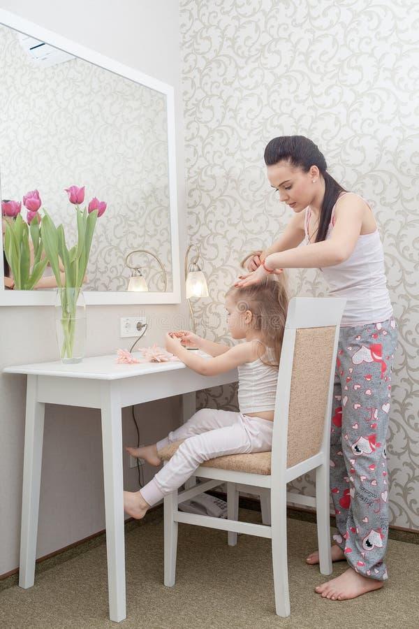 Moder som gör hennes lilla dotters hår royaltyfri foto