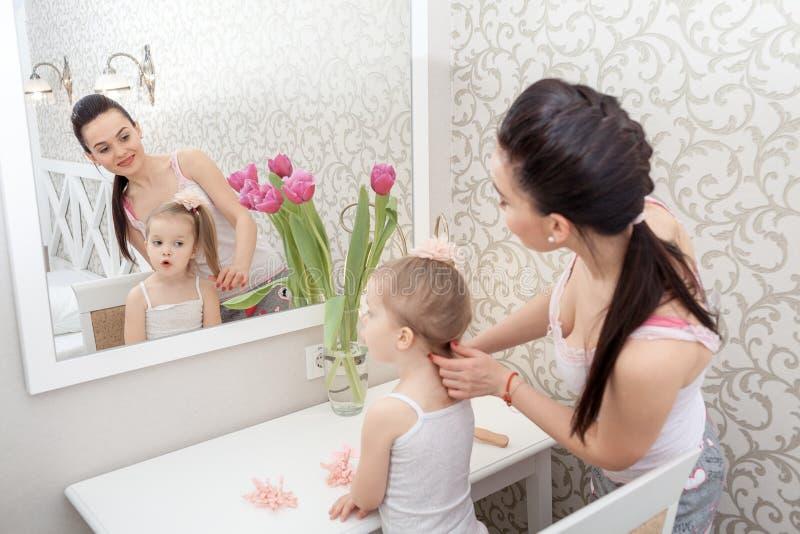 Moder som gör hennes lilla dotters hår fotografering för bildbyråer