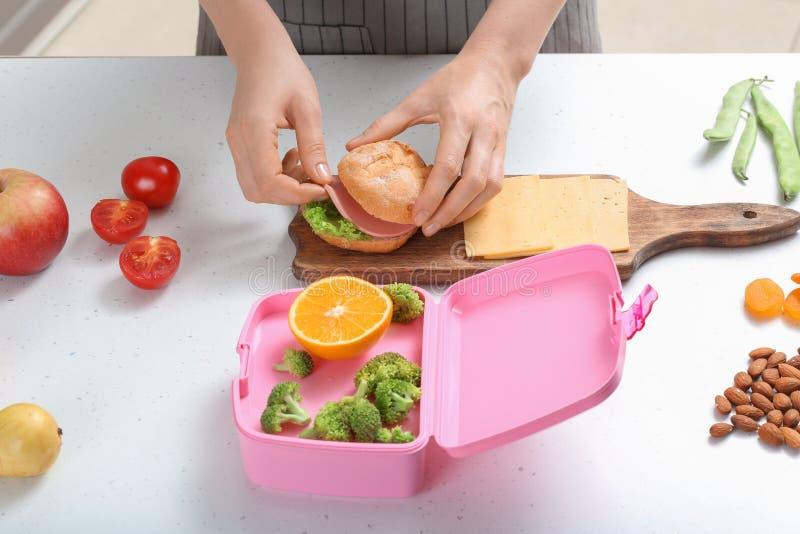 Moder som gör smörgåsen för skolalunch på tabellen i kök royaltyfri foto