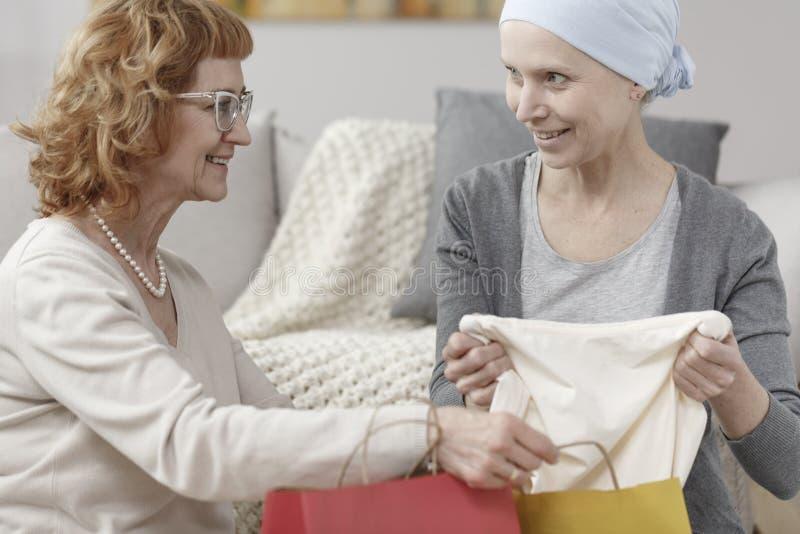 Moder som ger kläder till dottern royaltyfria foton