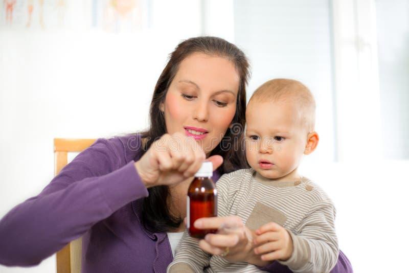 Moder som ger medicin för att behandla som ett barn royaltyfri fotografi