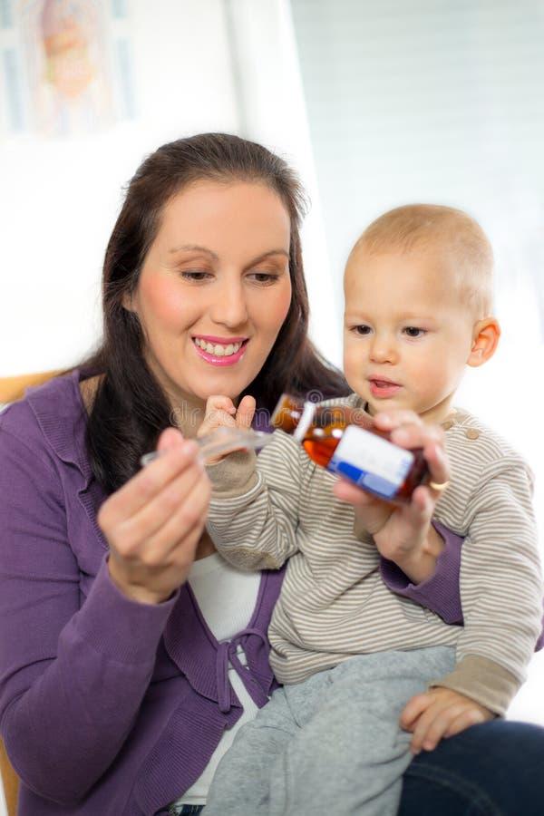 Moder som ger medicin för att behandla som ett barn arkivbild