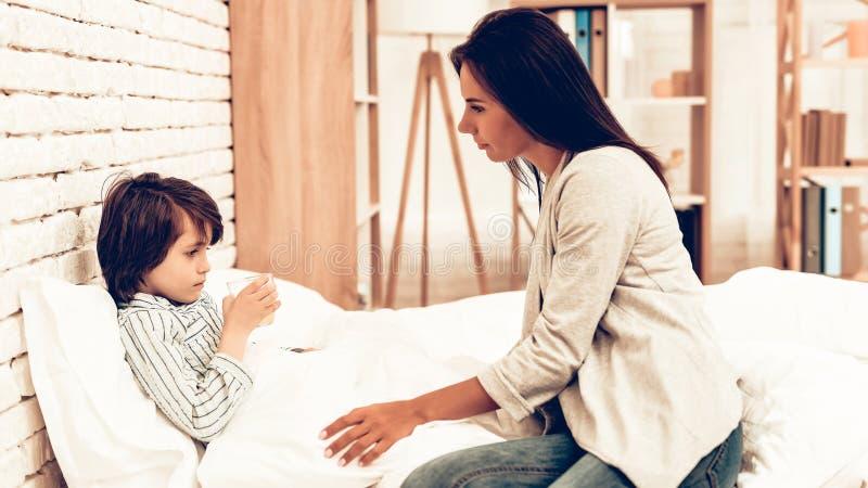 Moder som ger medicin till liggande säng för sjuk son arkivbild