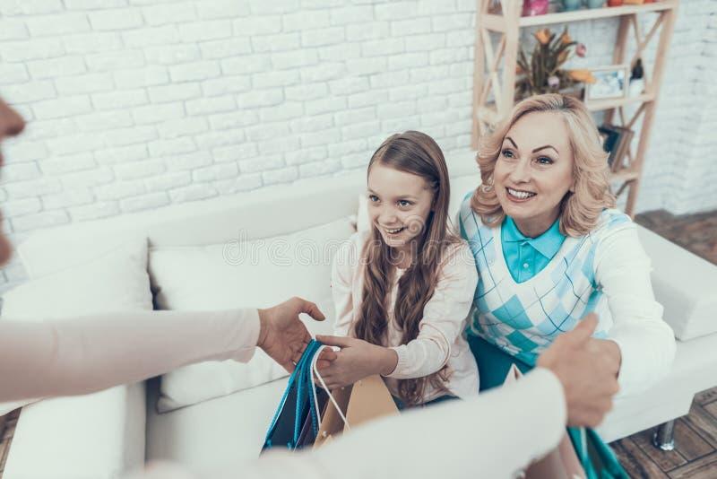Moder som ger packar med gåvor till den lyckliga familjen arkivbilder