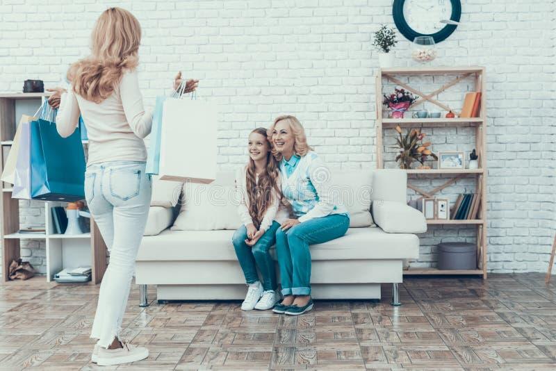 Moder som ger packar med gåvor till den lyckliga familjen arkivfoton