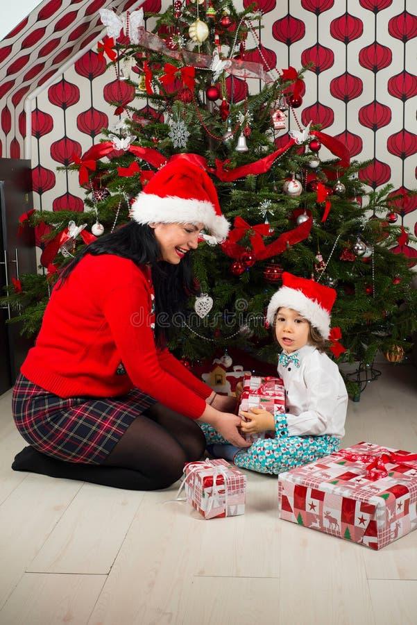 Moder som ger Xmas-gåva till hennes son royaltyfria foton