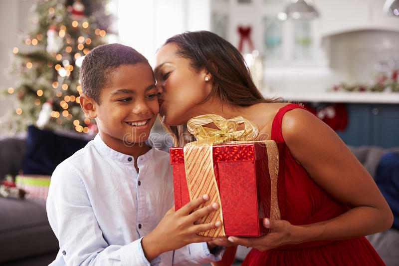 Moder som hemma ger julklappar till sonen royaltyfri foto