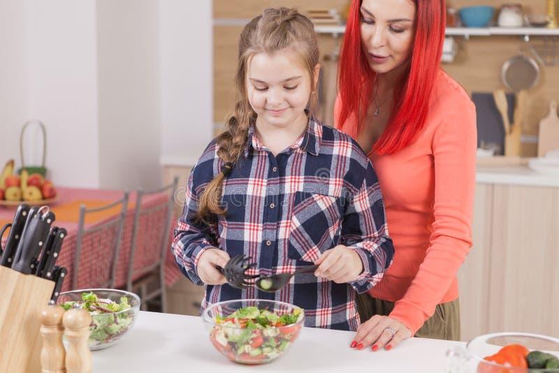 Moder som hjälper hennes dotter att blanda salladingredienser arkivbilder