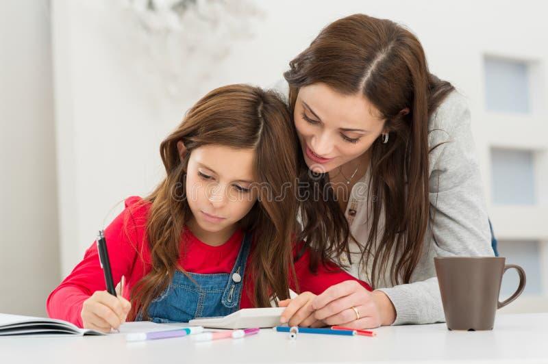 Moder som hjälper hennes dotter, medan studera royaltyfria bilder