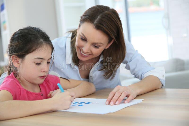 Moder som hjälper hennes dotterhandstil royaltyfria bilder