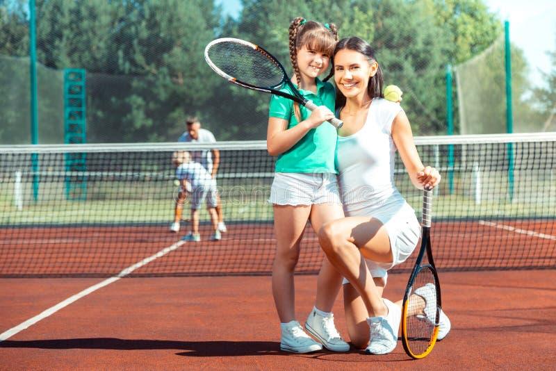 Moder som i huvudsak ler, innan att spela tennis med dottern royaltyfri foto