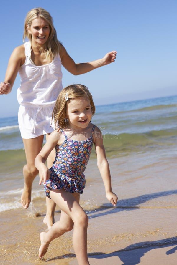 Moder som jagar dottern längs stranden arkivbilder