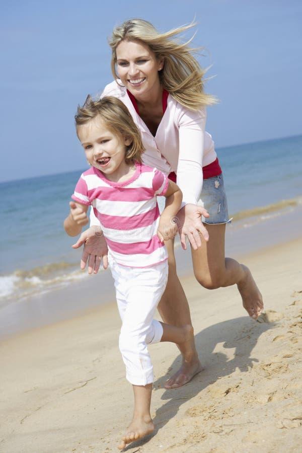 Moder som jagar dottern längs stranden royaltyfria foton
