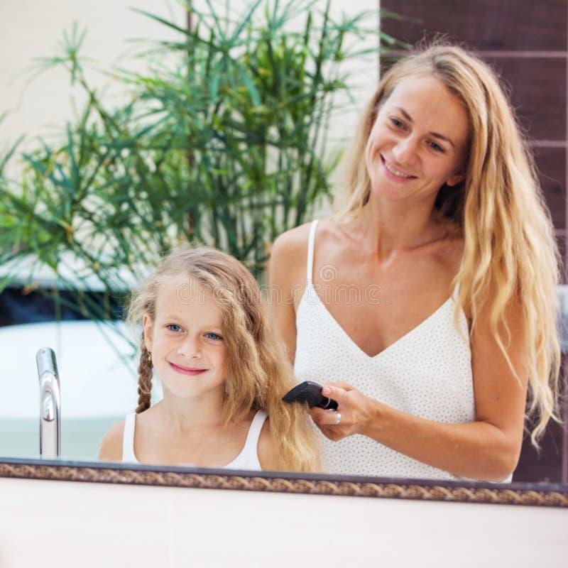 Moder som kammar dotterh?r royaltyfria bilder