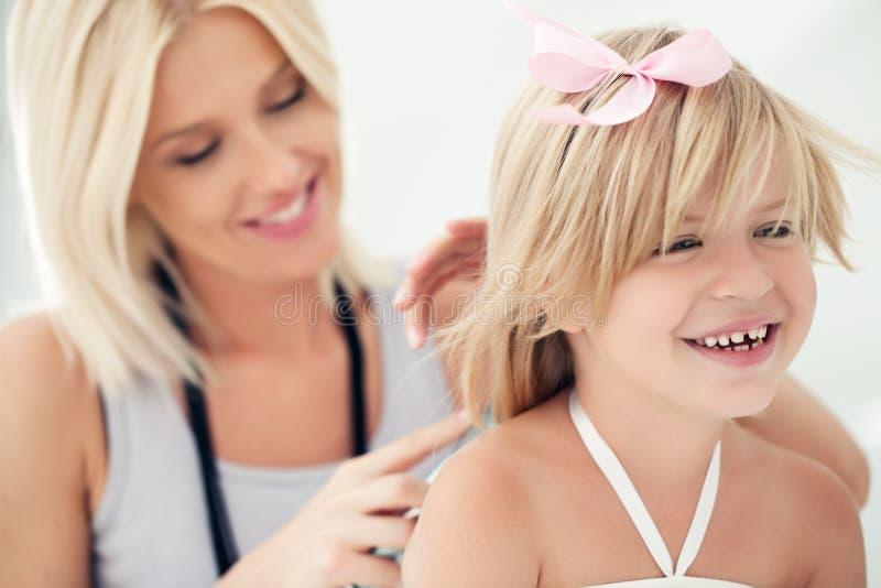 Moder som kammar dotters hår royaltyfri bild