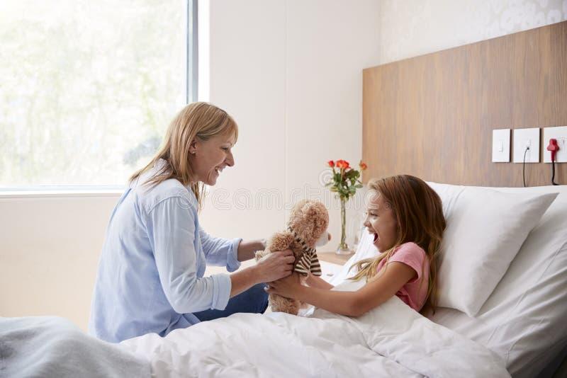Moder som kommer med dottern som ligger i gåva för sjukhussäng av Teddy Bear During Visit arkivbilder