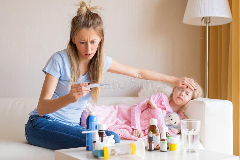 Moder som kontrollerar temperatur av hennes sjuka barn royaltyfria bilder