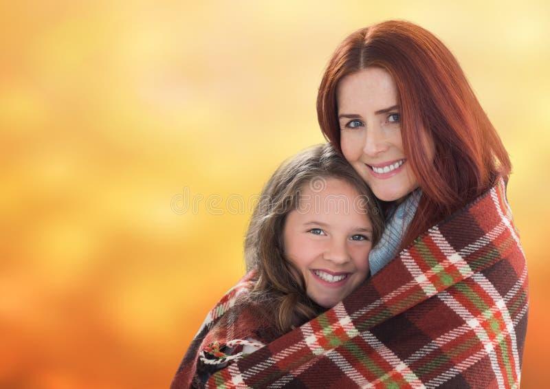 Moder som kramar dottern mot orange bakgrund royaltyfria bilder