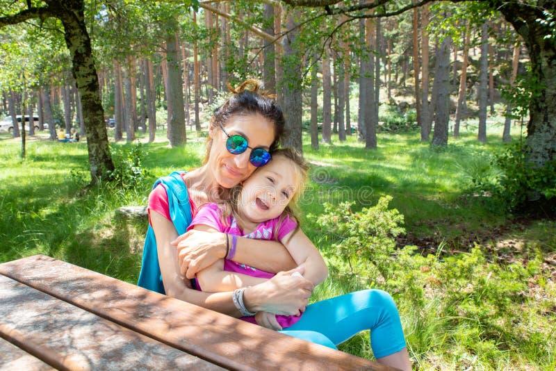 Moder som kramar hennes dotter som sitter på en picknickbänk i en skog av landet fotografering för bildbyråer