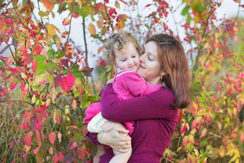 Moder som kysser hennes litet barndotter i trädgård arkivfoton